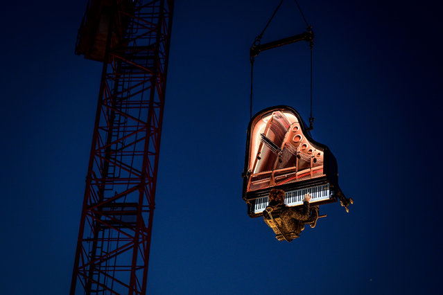 "Swiss pianist and composer Alain Roche performs ""Chantier"" suspended in the air with his grand piano under a moving crane at dawn on August 16, 2019 during the 20th ""Jeux du Castrum"", a multidisciplinary festival that takes place until August 18, 2019 in Yverdon-les-Bains. (Photo by Fabrice Coffrini/AFP Photo)"