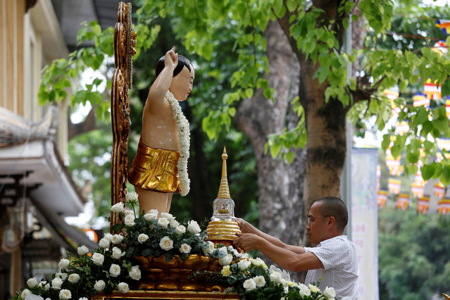 A man places a container holding what is believed to be the relics of Buddha in front of a Child Buddha statue while celebrating the Vesak Day in Quan Su Pagoda, Hanoi, Vietnam May 9, 2017. (Photo by Reuters/Kham)