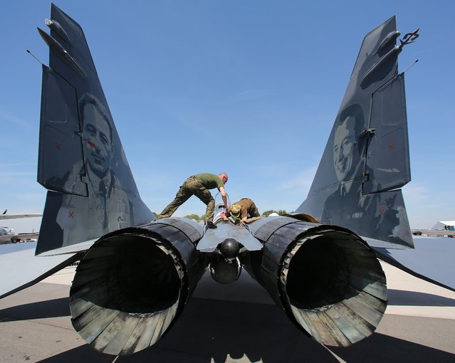 Two mechanics stand on a MIG-29 aircraft at the ILA Berlin Air Show 2014 in Selchow, Germany, 21 May 2014. The aerospace and defence industry exhibition takes place at the southern area of Berlin-Schoenefeld airport from 20 till 25 May 2014. (Photo by Wolfgang Kumm/EPA)