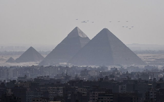 A picture taken from the 24th floor of a building in down town Cairo, shows three French made  Rafale fighter jets (front) flying with other Egyptian air force warplanes above the great pyramids in Giza, on the outskirts of the Egyptian capital, on July 21, 2015. Egypt took delivery of three Rafale fighter jets from France, the first of 24 warplanes sold in a 5.2 billion euro ($5.6 billion) deal earlier this year. (Photo by Khaled Desouki/AFP Photo)