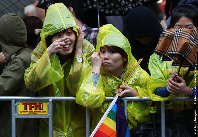 Crowd members attempt to keep dry with umbrellas and ponchos prior to the 2012 Sydney Gay & Lesbian Mardi Gras Parade