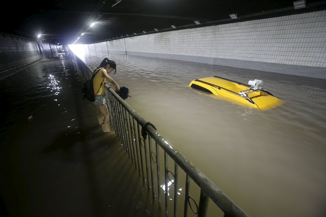 A woman walks past a stranded car as she tries to cross a flooded tunnel after heavy rainfall hit Wuhan, Hubei province, China, July 23, 2015. (Photo by Reuters/China Daily)