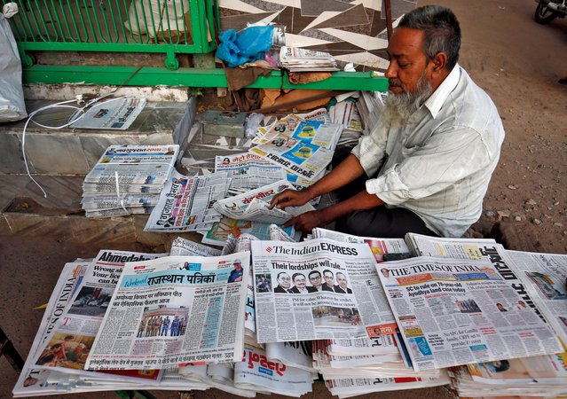 A vendor arranges newspapers with headlines about Supreme Court's verdict on a disputed religious site claimed by both majority Hindus and Muslim in Ayodhya, in Ahmedabad, India, November 9, 2019. (Photo by Amit Dave/Reuters)
