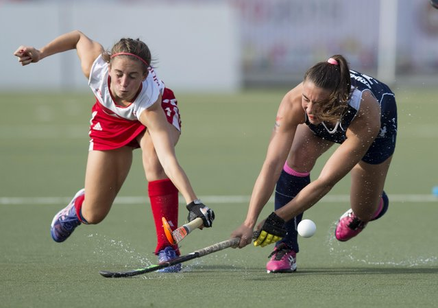 Canada'a Amanda Woodcraft, left, battles for the ball with Chile's Denise Krimerman, during the bronze medal final in women's field hockey at the 2015 Pan Am Games in Toronto, Friday, July 24, 2015. Canada defeated Chile to win the bronze medal. (Photo by Darren Calabrese/The Canadian Press via AP Photo)