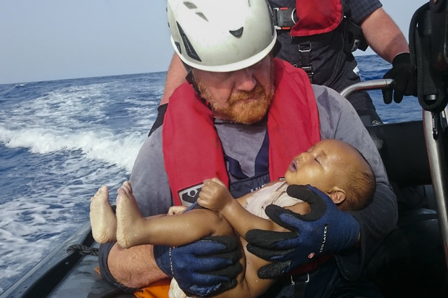 In this Friday, May 27, 2016 photo, a Sea-Watch humanitarian organization crew member holds a drowned migrant baby, during a rescue operation off the coasts of Libya. Survivor accounts have pushed to more than 700 the number of migrants feared dead in Mediterranean Sea shipwrecks over three days in the past week, even as rescue ships saved thousands of others in daring operations. (Photo by Christian Buttner/Eikon Nord GmbH Germany via AP Photo)