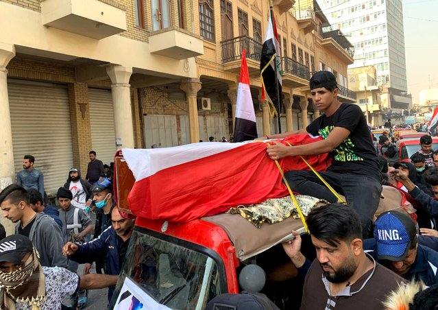 Mourners and protesters escort the flag-draped coffin of Munir Ali, whose family said was killed in anti-government demonstrations, during his funeral in Baghdad, Iraq, Sunday, November 24, 2019. (Photo by Ali Abdul Hassan/AP Photo)