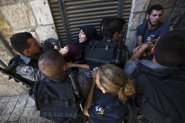 Israeli police and border police officers scuffle with Palestinian protesters in Jerusalem's Old City, on Tisha B'Av July 26, 2015. Masked rock-throwing Palestinians and Israeli police using stun grenades clashed on Sunday at al-Aqsa mosque plaza, on Tisha B'Av, the annual Jewish day of mourning for Jerusalem's two destroyed Biblical temples. (Photo by Amir Cohen/Reuters)
