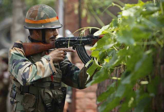 An Indian army soldier holds an AK-47 assault rifle during a fight in the town of Dinanagar, in the northern state of Punjab, India, Monday, July 27, 2015. (Photo by Channi Anand/AP Photo)