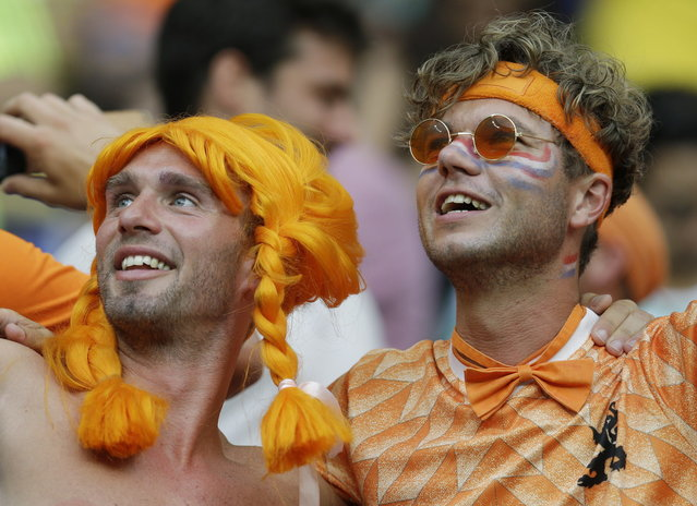 Dutch fans pose wearing colorful outfits during the group B World Cup soccer match between Spain and the Netherlands at the Arena Ponte Nova in Salvador, Brazil, Friday, June 13, 2014. (Photo by Natacha Pisarenko/AP Photo)