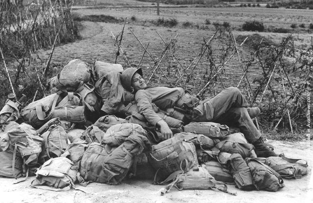 An American soldier relaxing on a heap of kit-bags, shortly after the invasion and capture of the Korean port of Inchon
