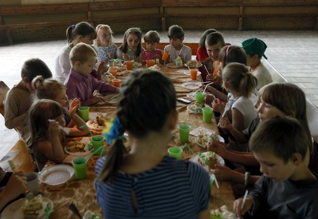 Children sit around a table during a birthday party at a health and rest centre which serves as a temporary accommodation for refugees from eastern regions of the country in the town of Korostyshiv, Zhytomyr region, Ukraine, July 30, 2015. (Photo by Valentyn Ogirenko/Reuters)