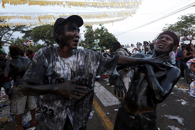 Devotees covered in motor oil play as they takes part in celebrations honoring the patron saint of Managua, Santo Domingo de Guzman, in Managua, Nicaragua August 1, 2015. (Photo by Oswaldo Rivas/Reuters)