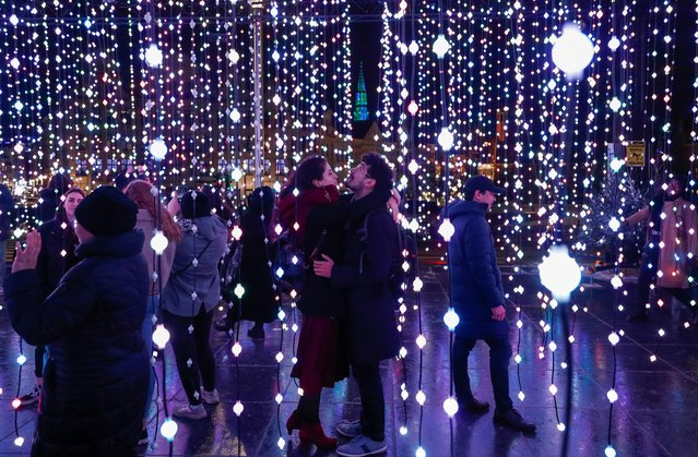 "A couple is seen inside an artistic light installation as part of the Christmas ""Winter Wonders"" festivities in central Brussels, Belgium on December 19, 2019. (Photo by Francois Lenoir/Reuters)"