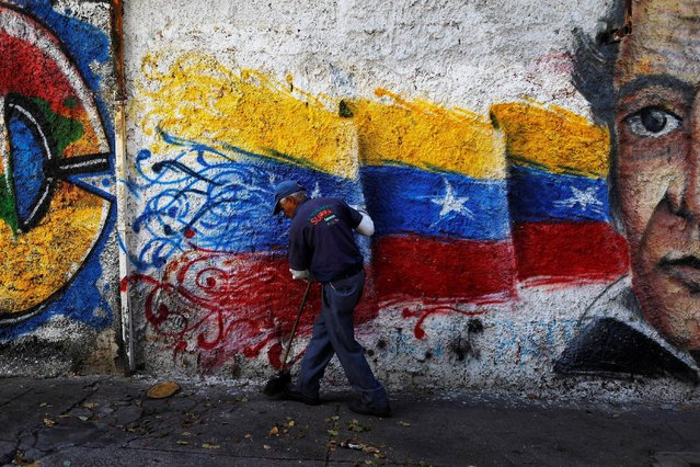 A street cleaner works in front of a graffiti with the colours of the Venezuelan flag, on a street in Caracas, Venezuela, June 8, 2016. (Photo by Ivan Alvarado/Reuters)