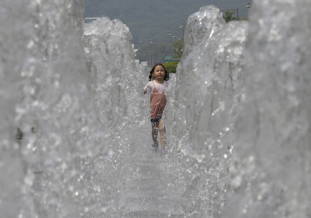 A girl runs through a public water fountain to cool herself in Seoul, South Korea, Friday, June 16, 2017. A heat wave warning was issued in Seoul as temperatures soared above 32 degrees Celsius (90 degrees Fahrenheit). (Photo by Ahn Young-joon/AP Photo)