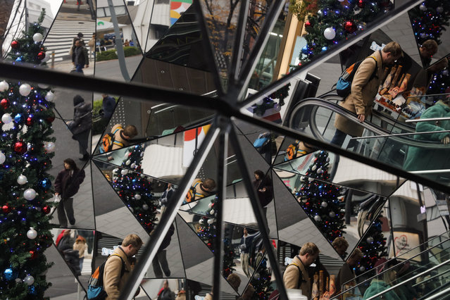 A Christmas tree and shoppers are reflected in the mirrored entrance of a shopping mall Tuesday, December 17, 2019, at the Harajuku district of Tokyo. (Photo by Jae C. Hong/AP Photo)