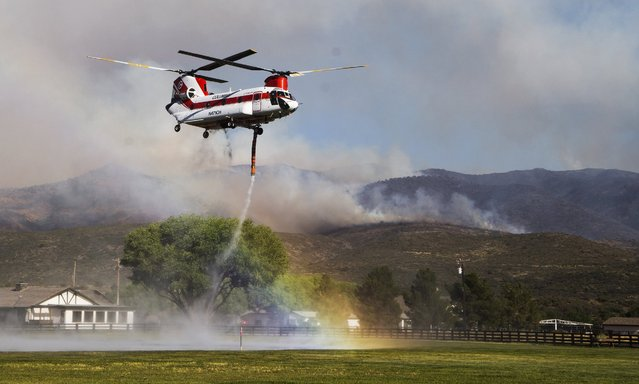 A rainbow forms as a helicopter picks up water to drop on the Tenderfoot Fire near Peeples Valley, Ariz., Thursday, June 9, 2016. A brush fire that began Wednesday pushed evacuations to several hundred as more people fled homes Thursday near Yarnell, an Arizona community. Authorities ordered additional evacuations Thursday, including homes in the Peeples Valley Area, as they feared the fire might make its way down to Highway 89. (Photo by Tom Tingle/The Arizona Republic via AP Photo)