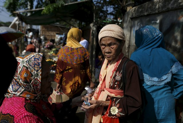A stallholder passes back change to her colleague at a vegetable market near Duri train station in Jakarta, Indonesia August 3, 2015. (Photo by Reuters/Beawiharta)