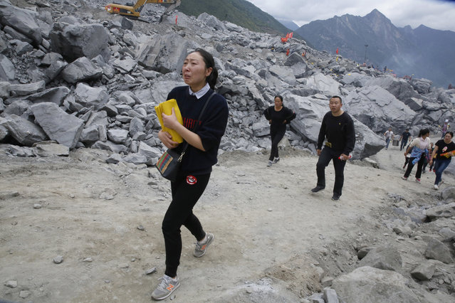 A woman tears up as she clutches paper offerings upon arriving at the site of a landslide in Xinmo village in Maoxian County in southwestern China's Sichuan Province, Sunday, June 25, 2017. Crews searching through the rubble left by a landslide that buried a mountain village under tons of soil and rocks in southwestern China on Saturday found bodies, but more than 100 people remained missing. (Photo by Ng Han Guan/AP Photo)