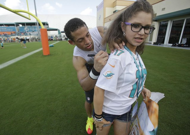 Miami Dolphins cornerback Brent Grimes autographs a shirt for Lexi Cornell, 11, of West Palm Beach, Fla., at NFL football training camp, Tuesday, August 4, 2015, in Davie, Fla. (Photo by Wilfredo Lee/AP Photo)