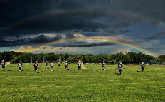 With the double rainbow in the background, Auburn and Marcellus 5th & 6th grade Upstate Lacrosse Association teams play a game at Auburn High School in Auburn, N.Y., Tuesday, June 27, 2017. (Photo by Kevin Rivoli/The Citizen via AP Photo)
