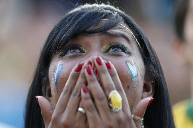 A fan of Brazil reacts while watching a broadcast of the 2014 World Cup semi-final against Germany at the Fan Fest in Brasilia, July 8, 2014. (Photo by Ueslei Marcelino/Reuters)