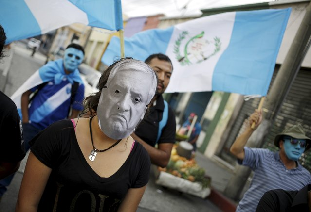 A woman wearing a paper mask with the image of Guatemala's President Otto Perez Molina along with demonstrators holding the Guatemalan flag protest to demand the resignation of Guatemala's President, outside of the City Congress in Guatemala City, August 8, 2015. Demonstrators are demanding the resignation of Guatemala's President Otto Perez Molina for the corruption scandals of politicians close to his government and his administration. (Photo by Jorge Dan Lopez/Reuters)