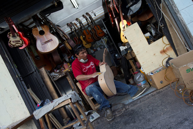 Ecuadorian luthier Ivan Ibujes prepares a guitar to be repaired at his shop in Quito, June 17, 2016. (Photo by Guillermo Granja/Reuters)