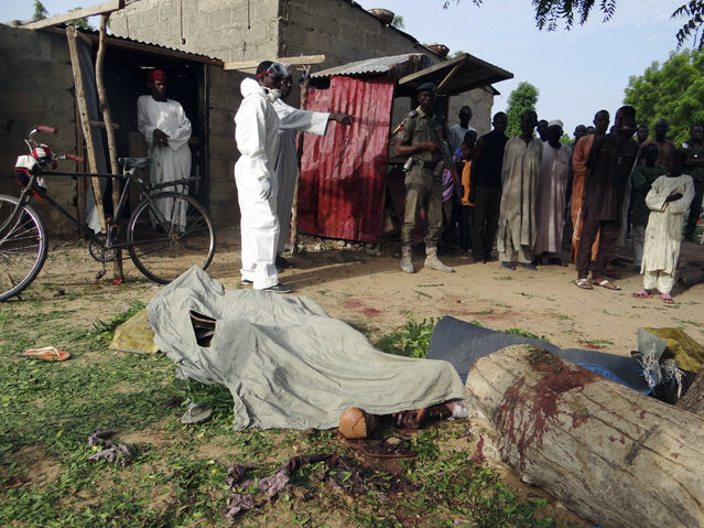 People mourn over the bodies of suicide bomb attack victims in a village near Maiduguri, Nigeria, Wednesday, July 12, 2017. Four Boko Haram suicide bombers killed over a dozen people in a series of attacks that targeted a civilian self-defense force and the people who gathered to mourn their deaths, police in Nigeria said Wednesday. It was the deadliest attack in months in the northeastern city of Maiduguri, the birthplace of Boko Haram's eight-year insurgency. (Photo by Jossy Ola/AP Photo)