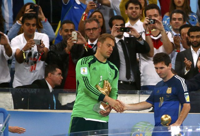 Germany's goalkeeper Manuel Neuer and Argentina's Lionel Messi shake hands after receiving the Golden Glove and Golden Ball awards respectively, after their 2014 World Cup final at the Maracana stadium in Rio de Janeiro July 13, 2014. (Photo by Michael Dalder/Reuters)
