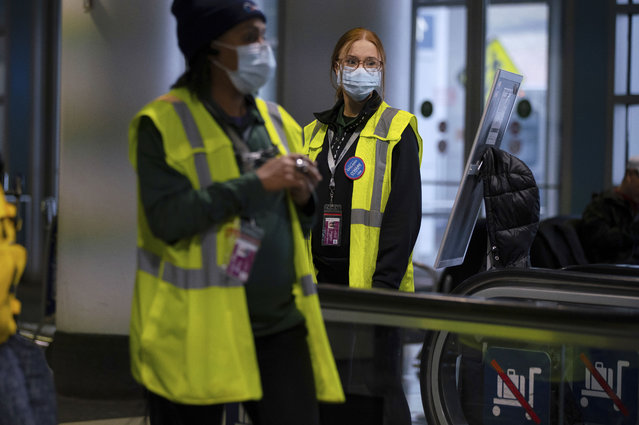 Airport employees wear face masks in Terminal 5 at O'Hare International Airport, Friday, January 24, 2020 in Chicago. A Chicago woman has become the second U.S. patient diagnosed with the dangerous new virus from China, health officials announced Friday. (Photo by E. Jason Wambsgans/Chicago Tribune via AP Photo)