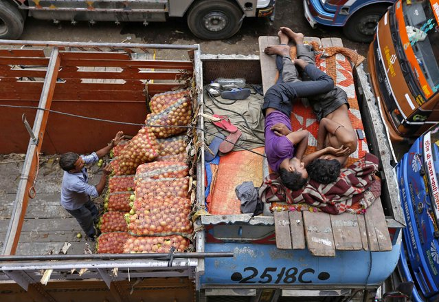 A worker unloads sacks of vegetables as men sleep on top of a truck at a wholesale vegetable market in the western Indian city of Ahmedabad July 14, 2014. India's wholesale price inflation in June eased to a four-month low of 5.43 percent, helped by slower increases in food and fuel costs, government data showed on Monday. (Photo by Amit Dave/Reuters)