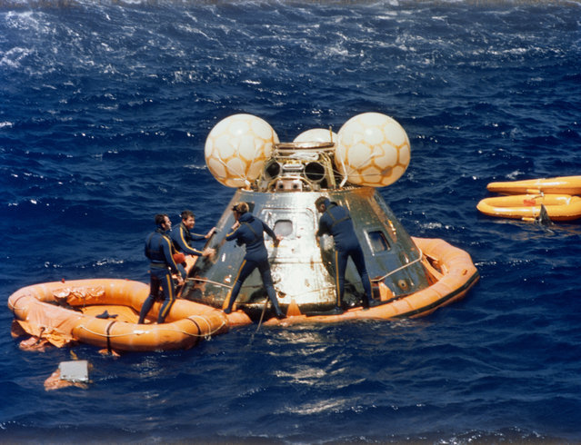 A team of U.S. Navy swimmers assists with the recovery of the ASTP Apollo Command Module following its splashdown in the Central Pacific Ocean to conclude the historic joint U.S.-USSR Apollo-Soyuz Test Project docking mission in Earth orbit, on July 24, 1975. The swimmers have already attached a flotation collar to the spacecraft. The CM touched down in the Hawaiian Islands area at 4:18 p.m. (CDT), July 24, 1975. (Photo by NASA)
