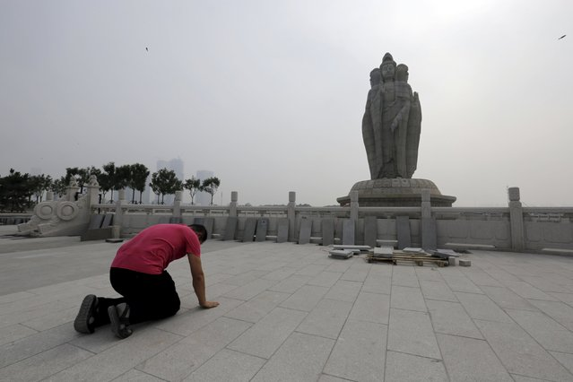 A man kowtows as he prays at Chaoyin Temple, Tianjin, China, August 14, 2015. (Photo by Jason Lee/Reuters)