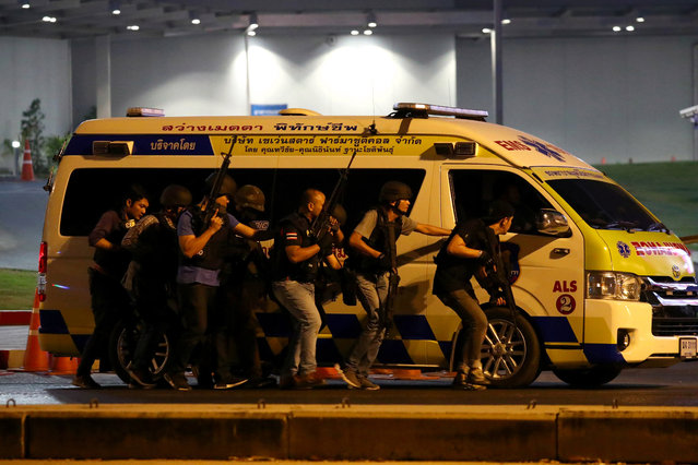 Thai security forces take cover behind an ambulance as they chase a shooter hidden in a shopping mall after a mass shooting in front of the Terminal 21, in Nakhon Ratchasima, Thailand on February 9, 2020. (Photo by Athit Perawongmetha/Reuters)