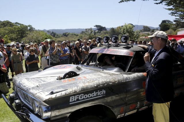 """Master of ceremonies, Alan Galbraith presents the """"Worst of Show"""" to a 1964 Ford Fairline at the Concours d'Lemon, part of the Pebble Beach Concours d'Elegance in Seaside, California, August 15, 2015. (Photo by Robert Galbraith/Reuters)"""