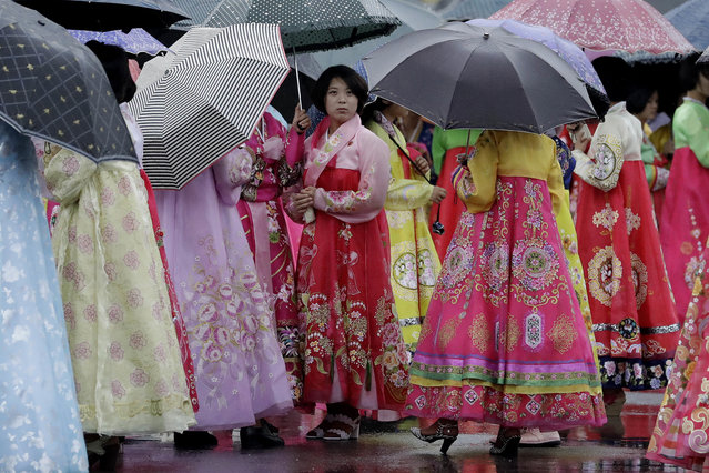 University students wearing traditional Korean dresses wait in the rain for the start of a mass dance on Thursday, July 27, 2017, in Pyongyang, North Korea as part of celebrations for the 64th anniversary of the armistice that ended the Korean War. (Photo by Wong Maye-E/AP Photo)
