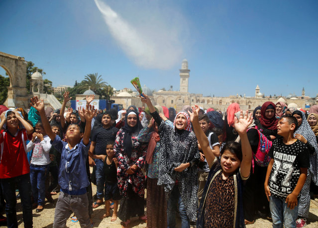Palestinian men spray water on children to cool them down before prayers on the last Friday of the holy month of Ramadan near the Dome of the Rock, on the compound known to Muslims as Noble Sanctuary and to Jews as Temple Mount, in Jerusalem's Old City, July 1, 2016. (Photo by Ammar Awad/Reuters)