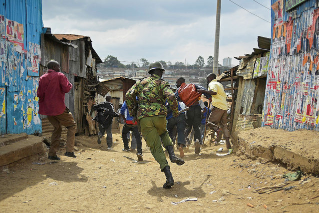 Kenyan police chase protestors in Mathare slum in Nairobi  on August 9, 2017, a day after general elections. (Photo by Carl De Souza/AFP Photo)