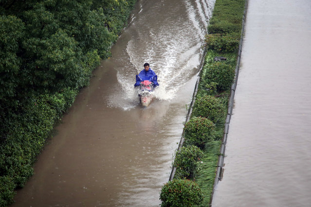 A rider drives past a flooded street in Changzhou, Jiangsu Province, China, July 2, 2016. (Photo by Reuters/Stringer)