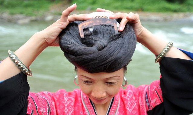 A woman combs her hair at the Huangluo Village of the Yao ethnic group in Guilin, south China's Guangxi Zhuang Autonomous Region, July 15, 2012. (Photo by Lu Boan/Xinhua)