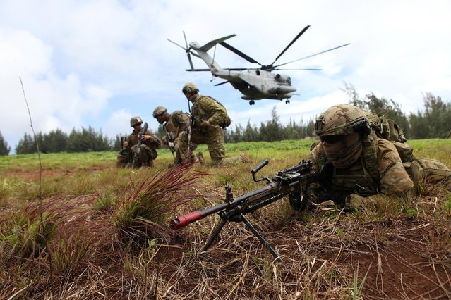Private Jessie Starks (R) of the Royal Australian Army 2RAR sets up a perimeter defense during a helicopter insertion exercise with US Marines in the Kahuku mountains training area during the multi-national military exercise RIMPAC in Honolulu, Hawaii, U.S. July 13, 2016. (Photo by Hugh Gentry/Reuters)