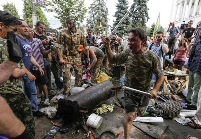 Protesters try to prevent municipal workers and volunteers from clearing away their tents at Independence Square in Kiev August 9, 2014. Tensions continued on Kiev's Independence Square, the scene of street protests that toppled a Moscow-backed president in February, as protesters still camped there clashed with city workers who tried to clear away their tents. (Photo by Konstantin Chernichkin/Reuters)