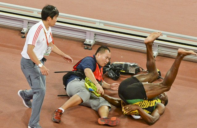 Usain Bolt of Jamaica (R) falls after being hit by a cameraman (C) on a Segway as he celebrates after winning the men's 200 metres final during the 15th IAAF World Championships at the National Stadium in Beijing, China, August 27, 2015. (Photo by Reuters/Stringer)