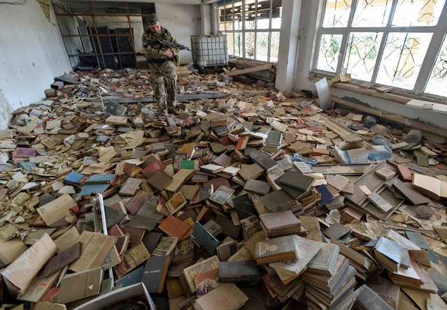 A Ukrainian serviceman inspects an abandoned library, with numerous books seen on the floor, near his position on the front line in the town of Maryinka, Ukraine September 3, 2017. Picture taken September 3, 2017. (Photo by Oleksandr Klymenko/Reuters)