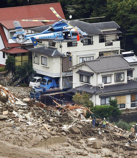 In this aerial photo, a survivor is lifted by a rescue helicopter from an area devastated by a massive landslide in Hiroshima, western Japan, Wednesday, August 20, 2014. (Photo by AP Photo/Kyodo News)