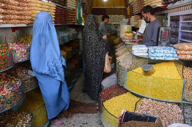 Afghan residents shop for dried fruit and sweets for the forthcoming Eid Al-Fitr holiday in Herat on July 4, 2016. Muslims around the world are preparing to celebrate the Eid al-Fitr holiday which marks the end of the fasting month of Ramadan. (Photo by Aref Karimi/AFP Photo)
