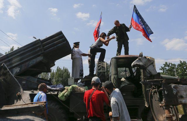 People holding flags of the self-proclaimed Donetsk People's Republic climb onto a seized Ukrainian army Grad multiple rocket launcher system that was destroyed in fighting, after it was placed on public display at the central square in Donetsk August 24, 2014. (Photo by Maxim Shemetov/Reuters)