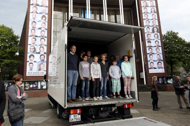 Seventy-one people stand in a truck during a public re-enactment referring to the 71 dead refugees found in the back of an abandoned truck, in Bochum, Germany September 2, 2015. (Photo by Ina Fassbender/Reuters)
