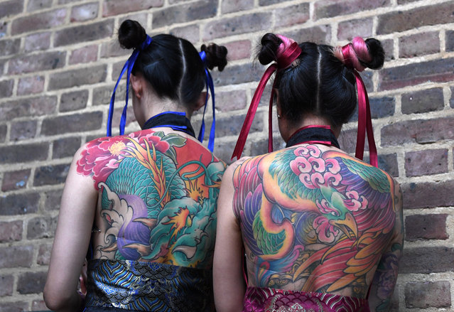 Tattoo enthusiasts pose for photographs during the London Tattoo Convention at the Tobacco Docks, in London, Britain, 24 September 2017. (Photo by Facundo Arrizabalaga/EPA/EFE)